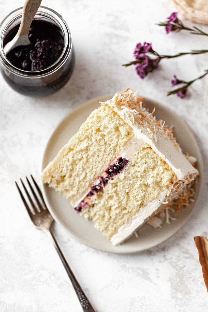 slice of coconut cake with berry compote