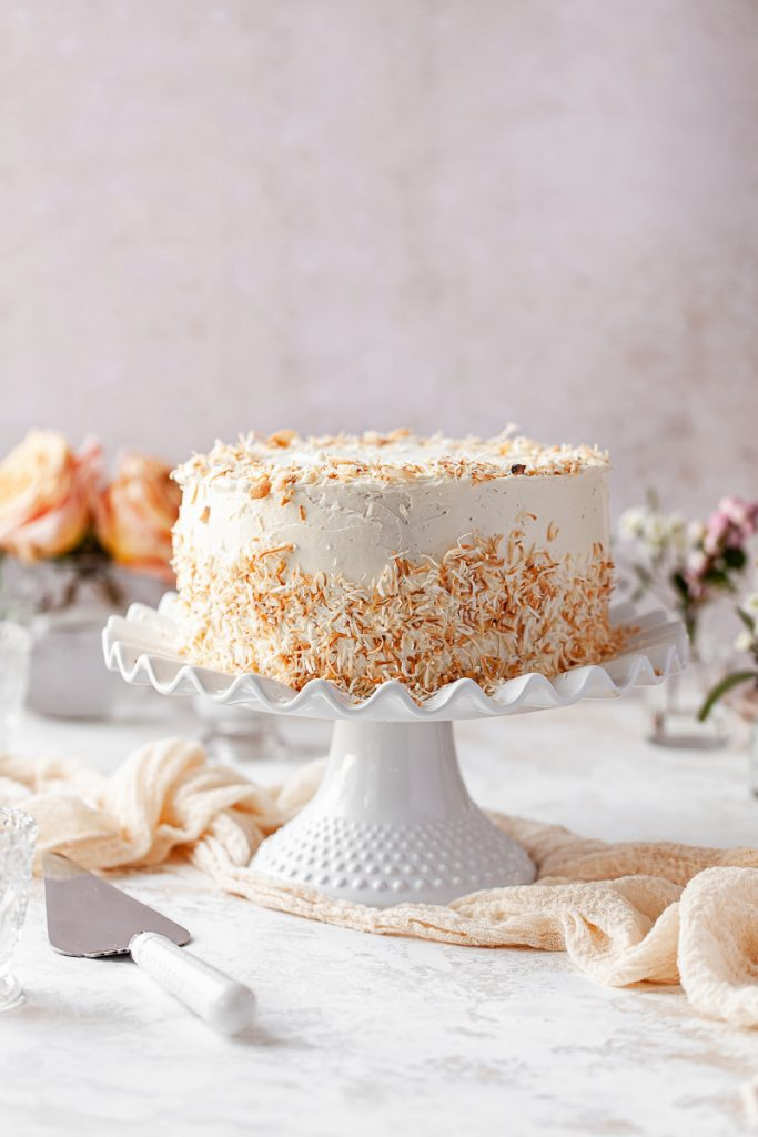 coconut cake with toasted coconut flakes on a cake stand