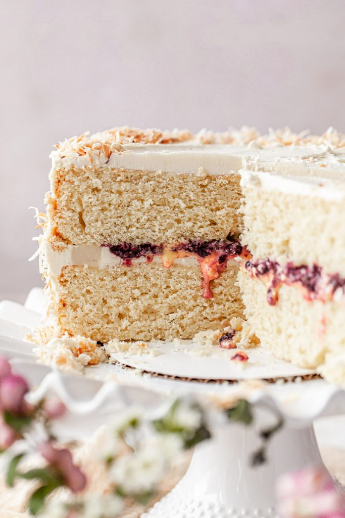coconut cake filled with berry jam on a cake stand